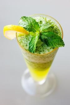 Fine del cocktail di mojito in su con i fogli di menta fresca