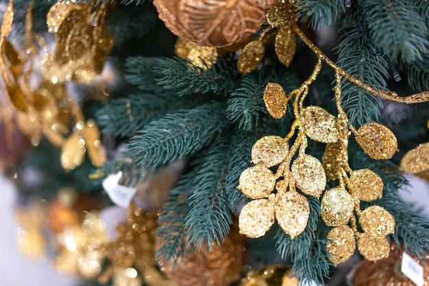 Fine dell'albero di natale in su con le decorazioni dell'oro
