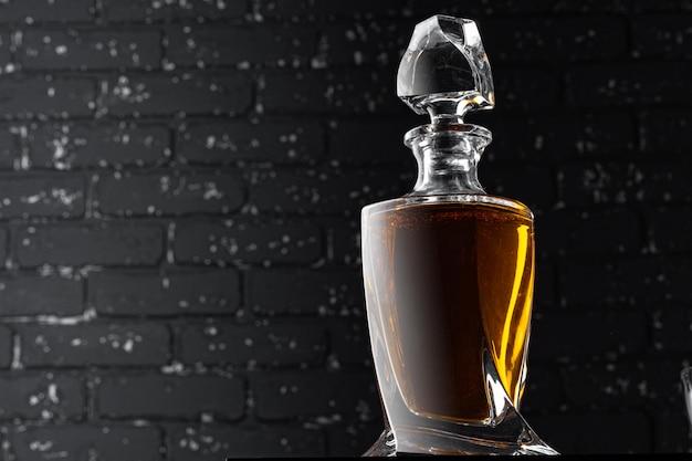 Fine della bottiglia di whisky in su contro la parete nera del grunge