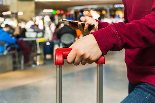 Fine della mano della ragazza su che tiene la maniglia rossa della valigia