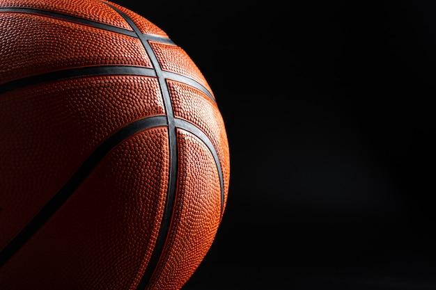 Fine della palla di pallacanestro su su superficie scura