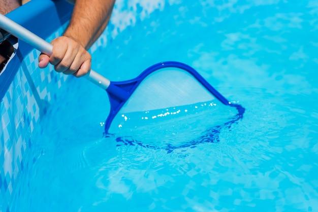 Fine di pulizia della piscina del giardino del cortile su