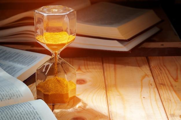 Fine dorata della clessidra della sabbia in su sulla tabella di lavoro