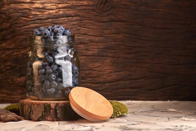 Fine fresca di vista frontale dei mirtilli sulla disposizione in barattolo di vetro sulla vecchia tavola di legno rustica bianca