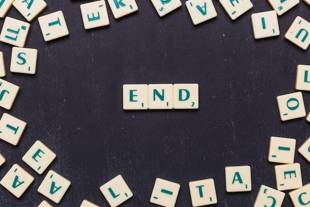 Fine lettere scrabble disposte su sfondo nero
