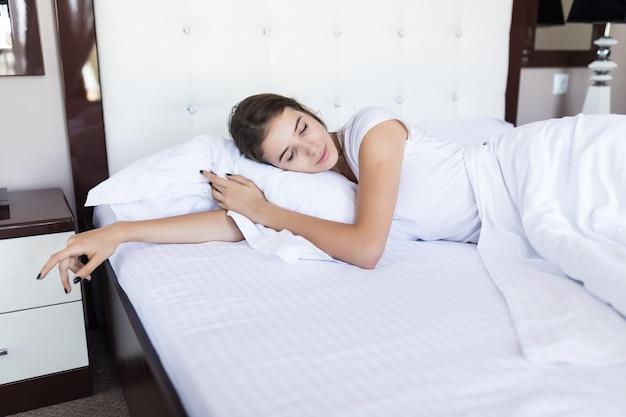 Fine settimana pigro mattutino per sorridente ragazza modello bruna in ampio letto con lenzuola bianche in hotel o appartamento di moda