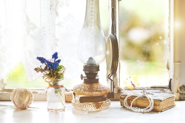 Finestra anteriore con lampada vintage e fiori di campo