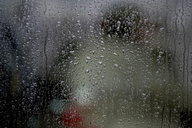 Finestra con gocce di pioggia su di essa sotto le luci