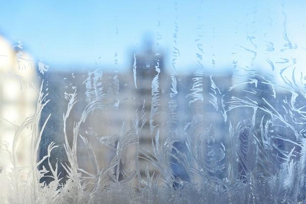 Finestra congelata di inverno con struttura brillante del modello del gelo del ghiaccio
