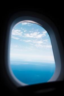 Finestra dell'aeroplano con il lanscape del mare e del cielo