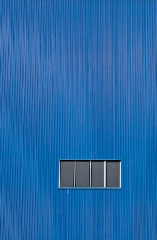 Finestra di fabbrica sulla parete blu. un estratto industriale