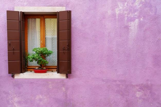 Finestra di legno d'annata sulla parete viola incrinata del cemento