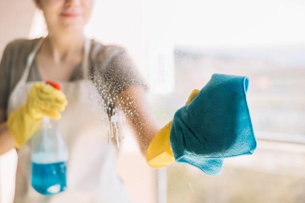 Finestra di pulizia della donna del primo piano