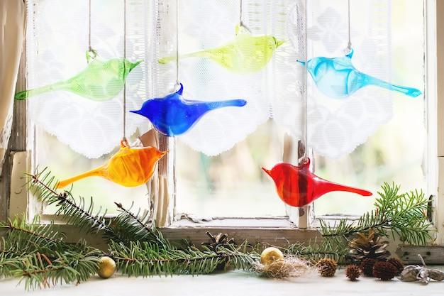 Finestra interna con gli uccelli e l'albero di natale di vetro