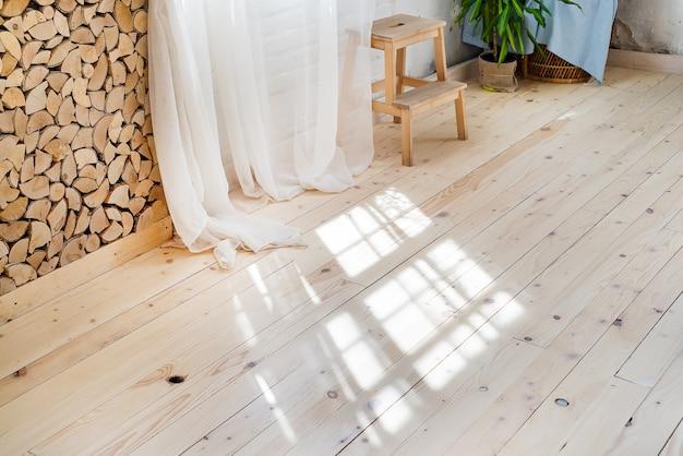 Finestre di vetro con tende bianche, fiori in una pentola sul pavimento e vista sugli alberi.