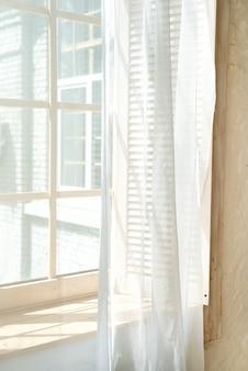 Finestre di vetro con tende bianche, luce del sole del mattino