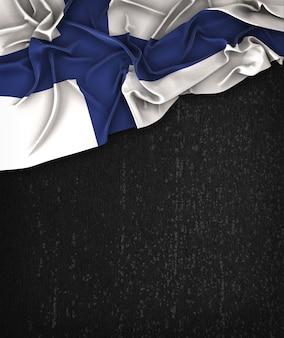 Finlandia flag vintage su una lavagna nera grunge con spazio per il testo