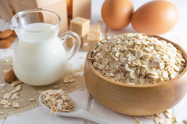 Fiocchi d'avena biologici, latte fresco e uova. concetto di colazione sana.