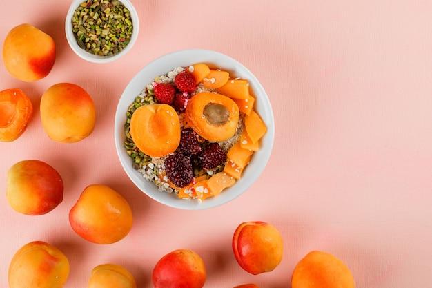 Fiocchi d'avena in una ciotola con pistacchio, albicocca, frutti di bosco