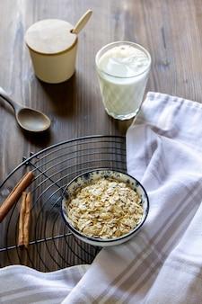 Fiocchi di avena vista laterale su un supporto con un bicchiere di latte cannella e zucchero semolato
