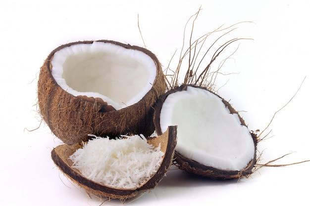 Fiocchi di cocco freschi collocati in corteccia e guscio isolato su sfondo bianco. vista frontale