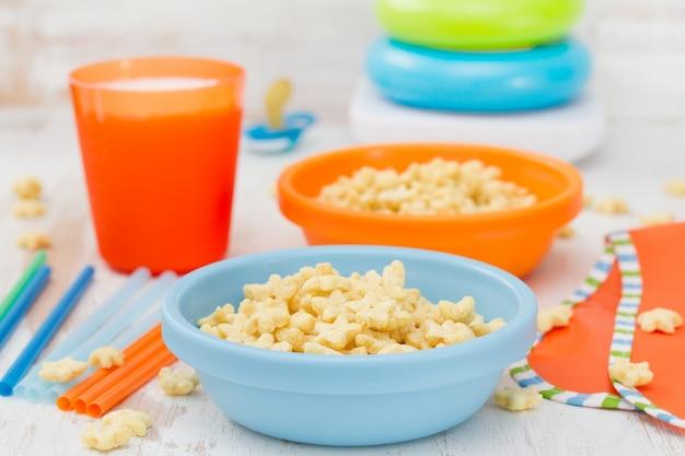 Fiocchi di mais in ciotola blu con latte su legno bianco