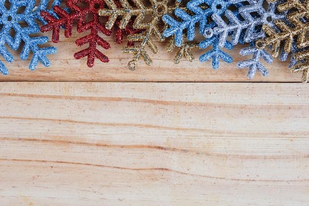 Fiocchi di neve colorate su fondo in legno con spazio di copia