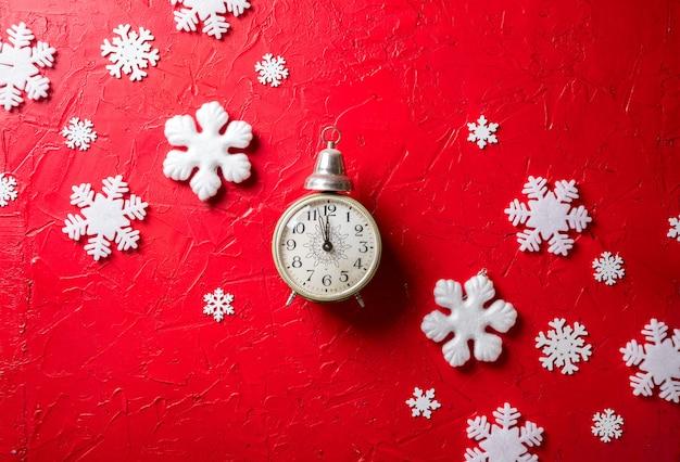 Fiocchi di neve di carta e orologio su sfondo rosso