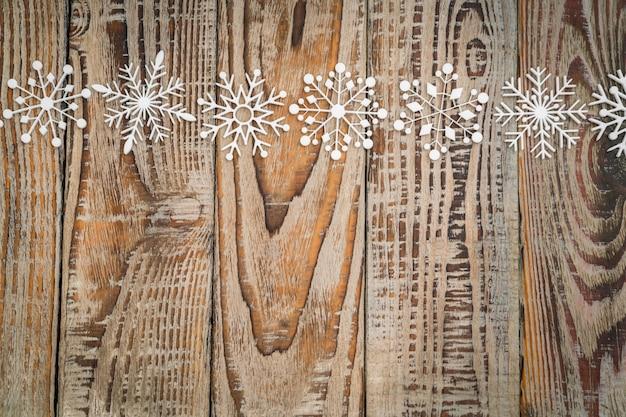 Fiocchi di neve di carta su fondo in legno.