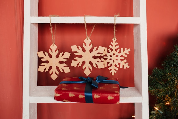Fiocchi di neve di natale e contenitore di regalo di legno con il nastro blu sulla scala a libro sulla parete rossa