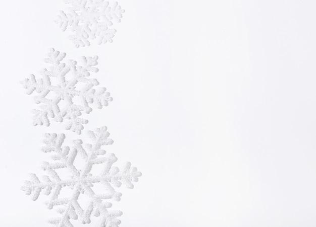 Fiocchi di neve sulla superficie bianca