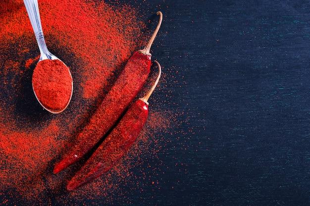 Fiocchi di peperoncino rosso e peperoncino in polvere scoppiano su sfondo nero