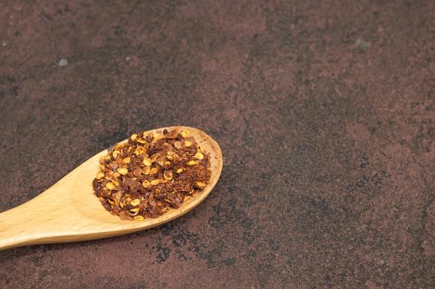 Fiocchi di polvere di peperoncino rosso piccante rosso schiacciato in cucchiaio di legno