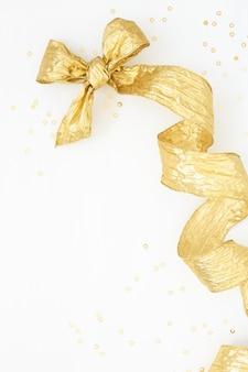 Fiocco d'oro e coriandoli d'oro su sfondo bianco