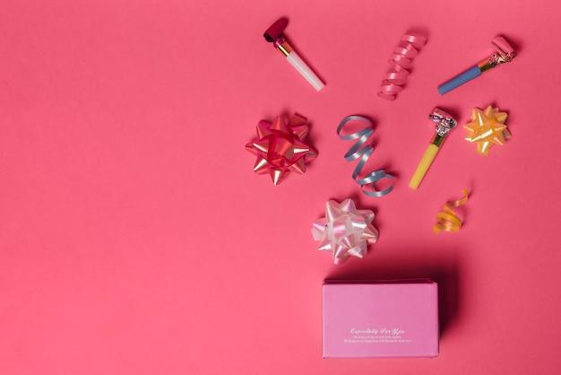 Fiocco di nastro; nastro di curling e soffiando le corna sopra la scatola rosa su sfondo rosa