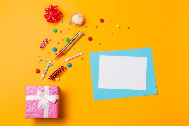 Fiocco di nastro rosso; aalaw; gemme; stelle filanti e spruzza con biglietto di auguri e scatola rosa su sfondo giallo