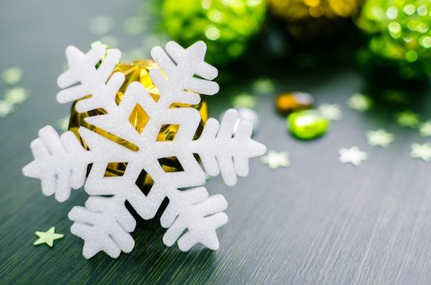 Fiocco di neve bianco su fondo di oro e bagattelle verdi di natale.