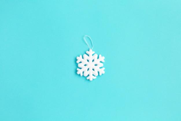 Fiocco di neve bianco su sfondo blu. composizione di natale.