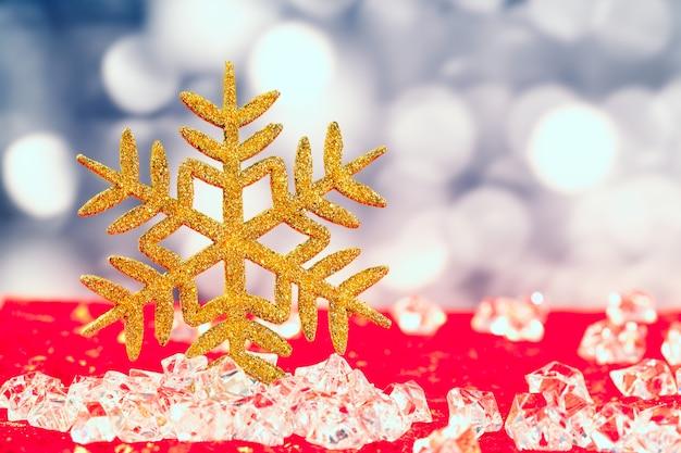 Fiocco di neve d'oro di natale su cubetti di ghiaccio