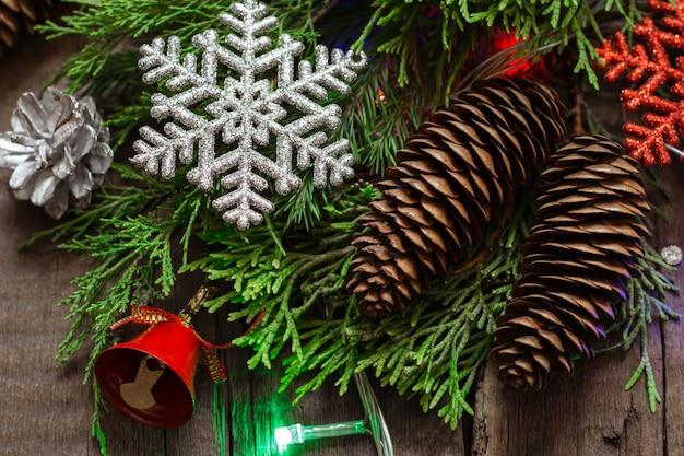 Fiocco di neve e coni scintillanti sullo sfondo di rami di conifere.