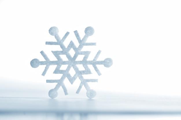 Fiocco di neve fatto di feltro isolato su un bianco