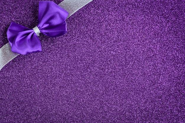 Fiocco viola con nastro d'argento su sfondo viola glitter. sfondo festivo.
