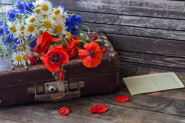 Fiordalisi, margherite, papaveri su una vecchia valigia, un vecchio foglio di carta su un tavolo di legno