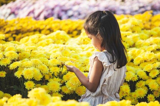 Fiore asiatico sveglio di amore della ragazza del bambino e divertiresi con il bello fiore nel giardino floreale