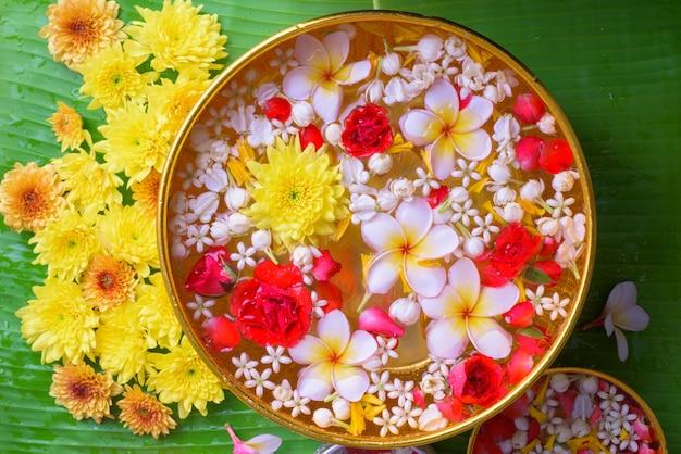 Fiore colorato in ciotole di acqua sulla foglia di banana