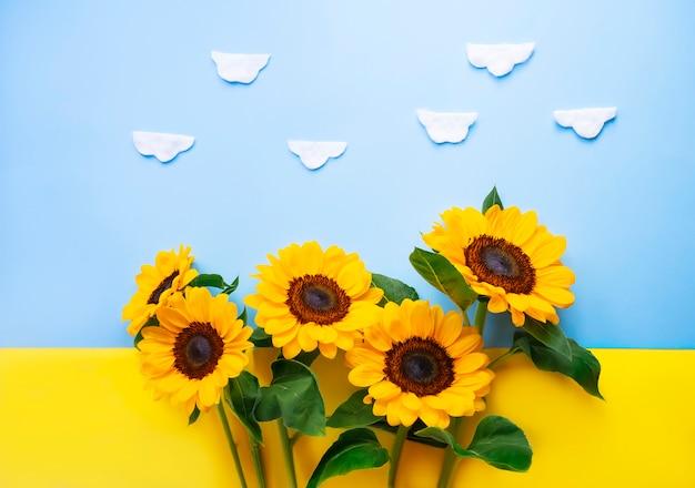 Fiore del sole isolato sopra una bandiera ucraina. piccoli girasoli luminosi su sfondo giallo e blu. mock up template. copia spazio per il testo