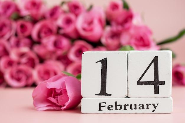 Fiore della rosa di rosa e calendario del 14 febbraio su fondo rosa. amore, romantico e felice giorno di san valentino concetto di vacanza