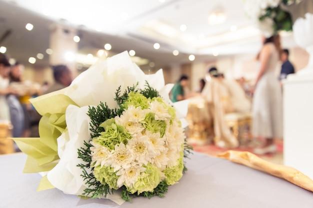 Fiore della sposa nel fondo della sfuocatura della festa nuziale