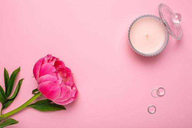 Fiore di peonia, candela e anelli. felice giorno di san valentino sfondo