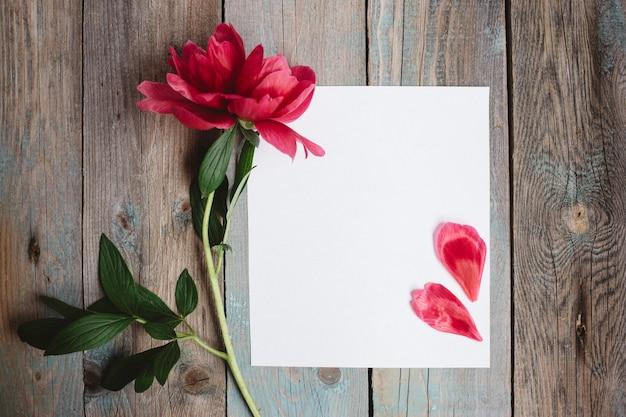 Fiore di peonia e foglio di carta bianca su fondo in legno